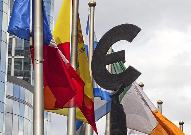 El símbolo del Euro entre las banderas española y griega, frente al parlamento de la Unión Europea en Bruselas (23/6/2011)