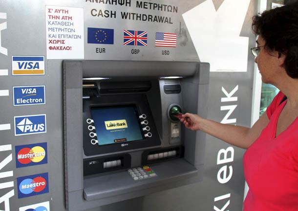 Una mujer saca dinero de un cajero automático (Chipre 25/6/2012).