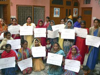 Grupo de mujeres muestran los diplomas en costura y bisutería, Nueva Delhi (La India, 2010)