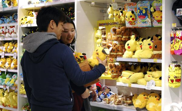 """JAPÓN POKÉMON ANIVERSARIO:GRA023. TOKIO, 24/02/2016.- Una pareja ojea un peluche de Pikachu en la tienda Pokémon Center Mega Tokyo del barrio de Ikebukuro en Tokio (Japón). La franquicia Pokémon celebra este sábado, 27 de febrero, el 20 aniversario del lanzamiento en Japón de los videojuegos originales """"Pokémon Rojo"""" y """"Pokémon Verde"""" para la Game Boy de Nintendo. EFE/María Roldán"""